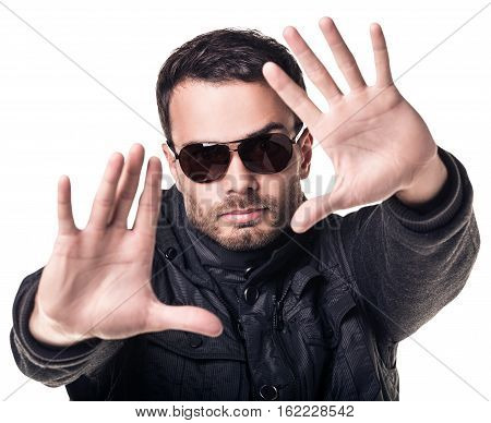 Handsome young man in sunglasses making stop sign over white background