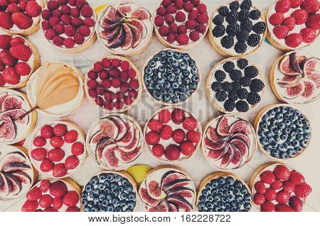 Fruit and berry tartlets dessert tray assorted top view background. Beautiful delicious tarts, pastry cakes sweets with fresh raspberries, figs, strawberry. French Bakery pattern. Filtered