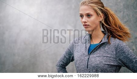 Fit Young Woman Standing Outdoors And Looking Away