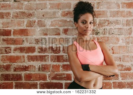 Portrait of young african woman in sports bra standing against brick wall with her arms crossed. Female fitness model in gym.