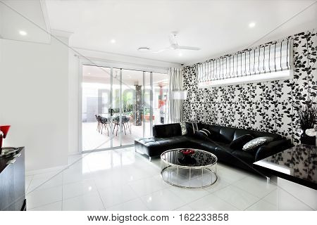 Modern living room that includes a black sofa with pillows and a creative round table like a drum. There are fruits in a vase. The walls are white. The room has a window with curtain and glass door to enter the outside patio area.