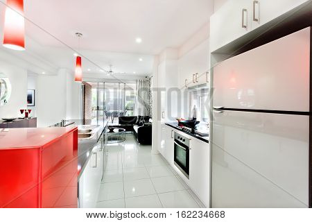 Inside view of a modern mansion through the kitchen focusing the refrigerator from the right side very closely. Countertop and a oven fixed to the white cupboards there are fancy red lights hanging on the ceiling and flashing.
