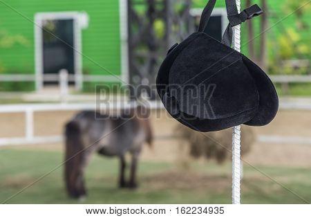 Helmet jockey hang on iron pole at training stable