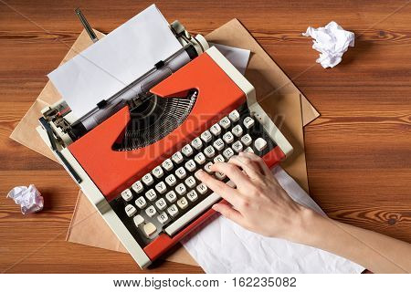 Top view of woman hand typing on red vintage typewriter with white blank paper sheet on wooden table