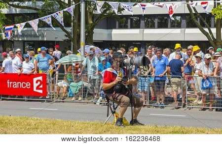 UtrechtNetherlands - 04 July 2015: Unidentified photographer setting his tool on the roadside before the apparition of the cyclists during the first stage of Tour de France in Utrect Netherlands on July 4 2015.