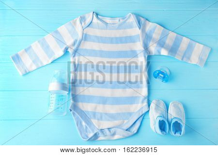 Baby clothes and necessities on wooden background