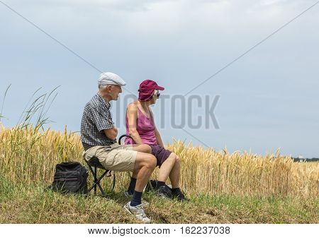 QUIEVYFRANCE- JULY 07 2015: Unidentified old couple sitting by the wheat field and waiting for the peloton during the stage the stage 4 of Tour de France in Quievy on 07 July 2015.