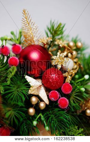 Christmas holiday centerpiece decor with fir branches golden leaves red berries and white candle. Closeup detail.