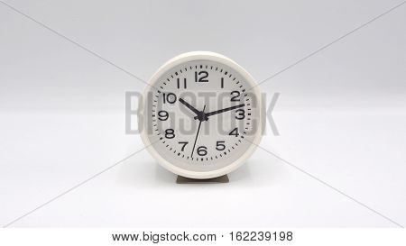 White clock with minute hand and hour hand on white background.
