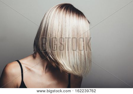 Model with unrecognizable face with blond shiny hair. Woman bob haircut styling. poster
