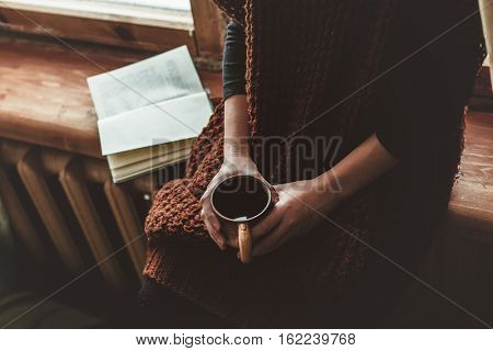 Girl in warm woolen sweater seating on window sill, drinking tea and reading a book. Winter weekends in old log house. Cold snowy weather. Cozy homely concept.