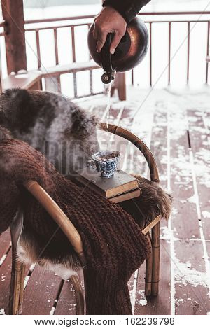 Chair with fur cover on a porch deck of a log cabin with snow. Making hot tea. Cold winter relax weekend