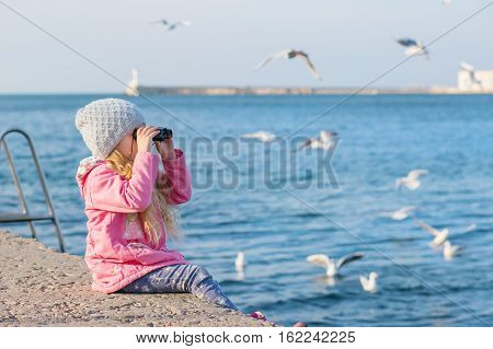 little girl looking through binoculars on the background of the sea