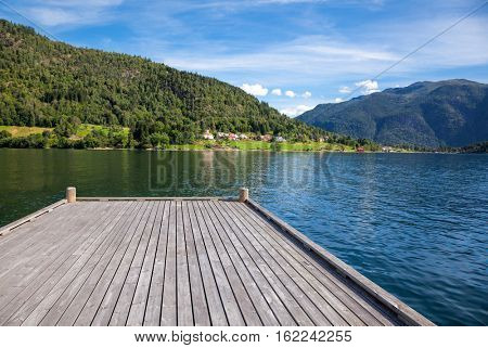 Wooden pier at norwegian fjord on a sunny summer day