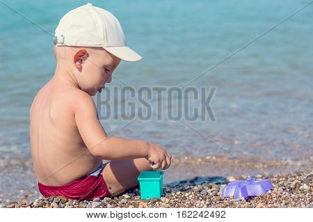 cute toddler boy playing on the beach in summer