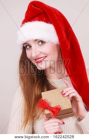 Cheerful woman wearing santa claus hat holding golden gift box with red bow. Christmas time giving and happiness concept.