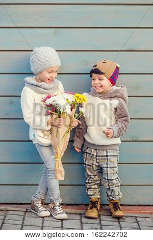 two happy little kid with a bouquet of flowers outdoors