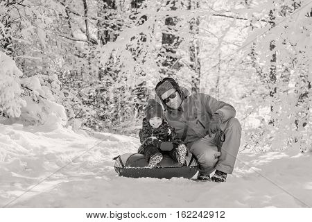Happy Toddler boy with dad in the snowy forest outdoors ( black and white )