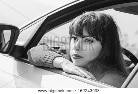 attractive young woman driving a car on a sunny day ( black and white )