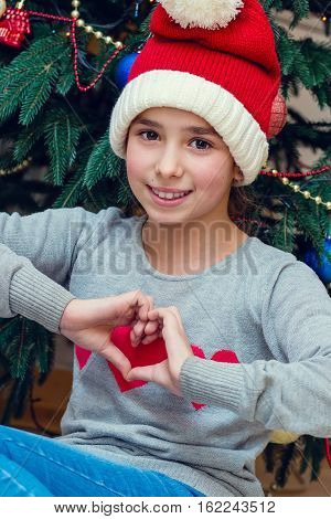 Christmas portrait of the girl in a striped hat of Santa Claus