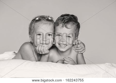 happy little sister hugging her brother lying ( black and white )