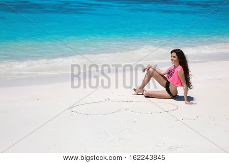 Carefree Bikini Model Girl With Heart On Sand Relaxing On Exotic Beach Beside Blue Water By Seashore
