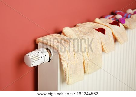 Warm knitted mittens drying on heating radiator on pink wall background