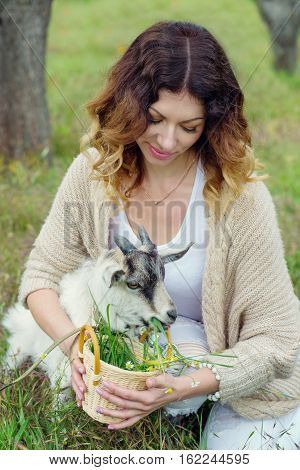 Beautiful young woman feeding goat grass outdoor