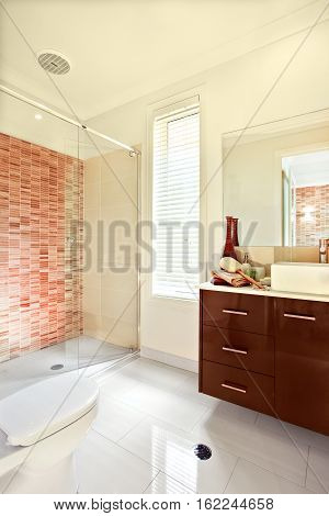 Luxury bathroom has white floor tiles exposed to the sunlight. The brown wooden cabinet has drawers and counter top with washstand in front of the mirror the wall is decorated with some color pattern