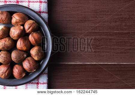 Hazelnuts on a plate with old kitchen dishcloth. Brown natural table. Flat lay top view. Copy space on the right. Vegetarian food concept.