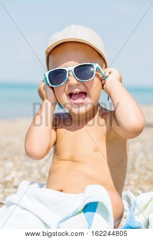 Happy Toddler baby sea trying on sunglasses sitting on a towel