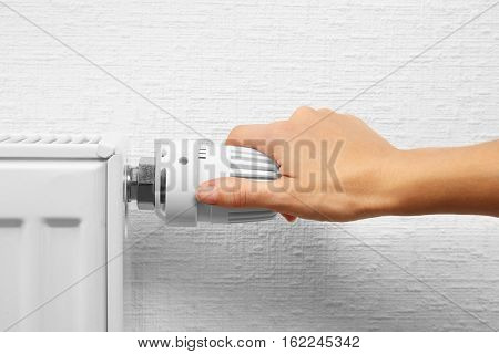 Woman holding temperature knob of heating radiator