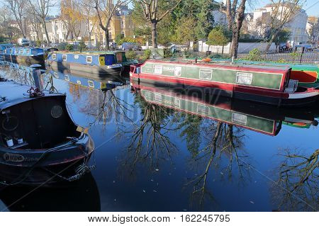 LONDON, UK - NOVEMBER 30, 2016: Reflections in Little Venice with colorful barges along canals