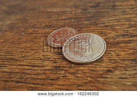 Macro detail of Croatian coins (Kuna and Lipa, HRK) on the wooden desk as a financial background of currency used in Croatia