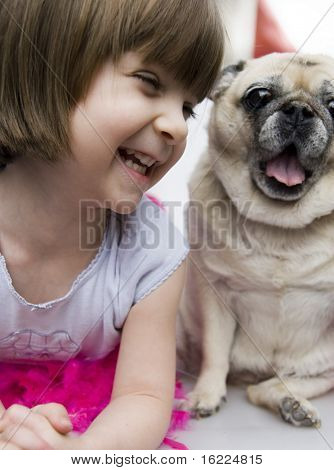 A lovely adorable young child with sweet smile looking at her pet pug dog poster