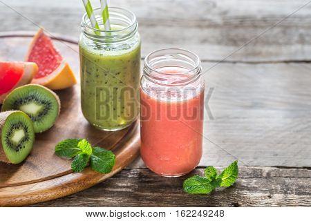 Glass jars of kiwifruit and grapefruit smoothies
