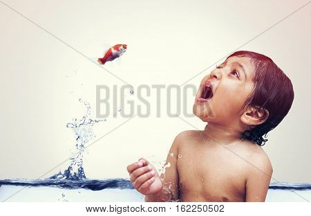Goldfish jumping out of water directly into the kids mouth isolated on white