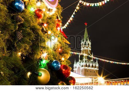 Christmas Fair. Decorated Christmas tree. Bright lights garlands. The festive mood. Red and gold balloons ribbons and flowers. Fair on the Red Square. The Spasskaya Tower.