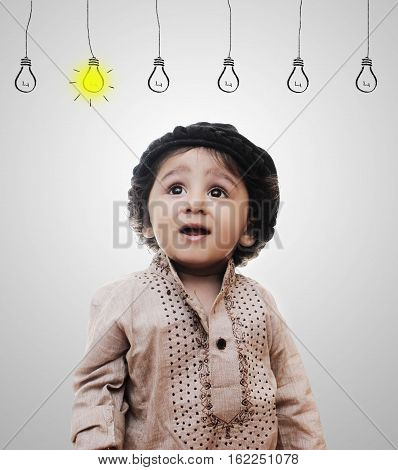 Adorable Intelligent Little Boy Thinking Idea Bulbs While Standing Before A White Background; Thinking Process With Chalk Board