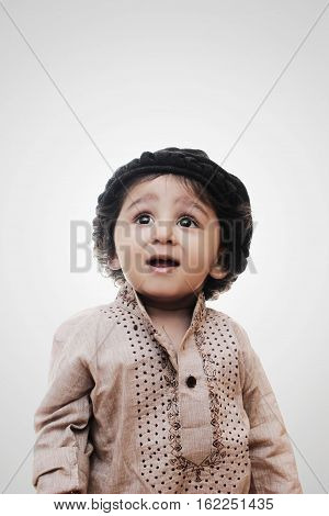 Adorable Intelligent Little Boy Thinking While Standing Before A White Background; Thinking Process With Chalk Board