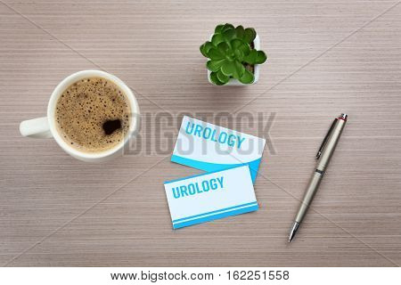 Cards with word UROLOGY, cup of coffee and pen on light wooden background, top view