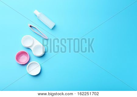 Container for contact lenses, tweezers and bottle of solution on blue background, close up view