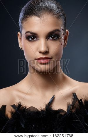 Closeup portrait of elegant attractive woman with black boa and party makeup with strasses.