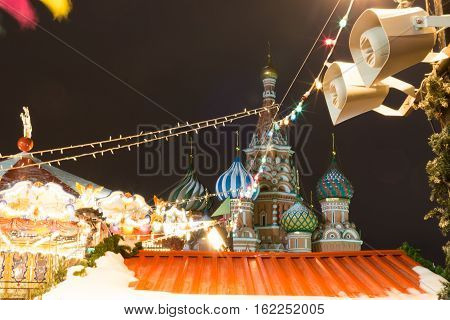 Christmas Fair. Bright lights garlands. The festive mood. Fair on the Red Square. St Basil's Church. Fairground lights