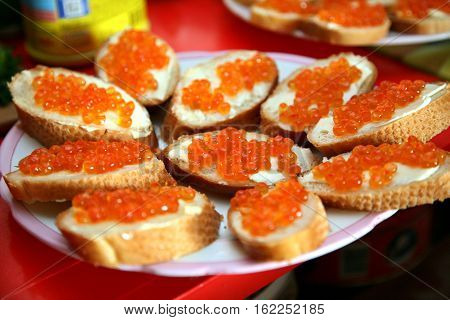 Sandwich with red caviar on white bread. Festive Christmas table with refreshments to celebrate the New year. Selective focus on middle of plate