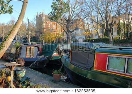 LONDON, UK - NOVEMBER 30, 2016: Little Venice with colorful barges along canals and Catholic Apostolic Church in the background