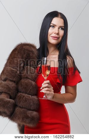 Portrait of girl in mink coat and red dress with glass of champagne on empty gray background