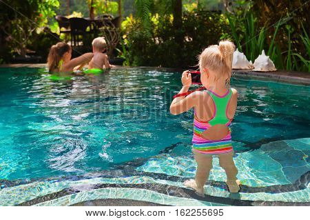 Happy family. Mother baby swim with fun in swimming pool relax at pool side. Girl take picture by photo camera. Healthy lifestyle active parent people recreation on beach summer holiday with child