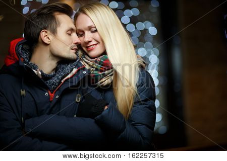 Beautiful spouses winter on the street on a background of night lights