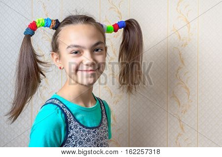 portrait of a smiling 11 year old girl with funny tails